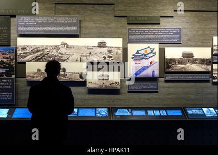 A man examines an information display inside the Zhengyangmen arrow Tower museum, Beijing - Stock Image