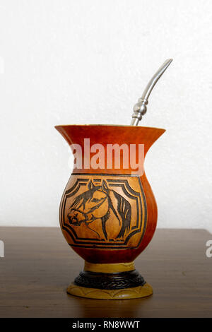 A gourd container (cuia) used to drink the Brazilian traditional mate-based  drink  (chimarrao) on wooden table against white background, side view - Stock Image