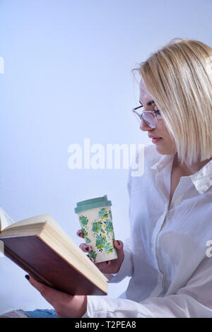 Young student girl reading book and drinking hot tea from retro cup. Woman with glasses isolated on white background in studio. Education concept - Stock Image