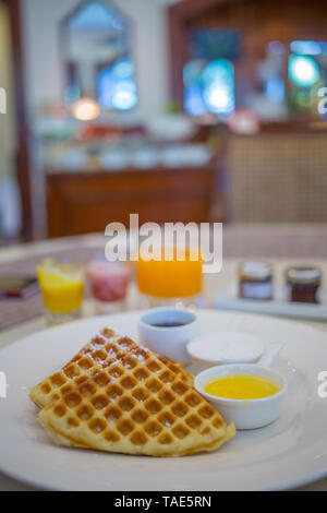 A hotel breakfast plate with Belgian waffles on it. - Stock Image