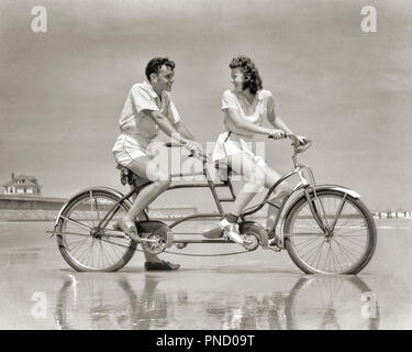 1940s YOUNG COUPLE IN WHITE SPORTS CLOTHES RIDING TANDEM BICYCLE AT SEASHORE ON WET BEACH WOMAN SMILING LOOKING BACK AT MAN  - b4135 HAR001 HARS HEALTHY YOUNG ADULT BALANCE SAFETY SEXY TEAMWORK ATHLETE JOY LIFESTYLE FEMALES MARRIED BIKING SPOUSE HUSBANDS ATHLETICS COPY SPACE FULL-LENGTH LADIES PERSONS MALES RISK ATHLETIC BICYCLES TRANSPORTATION EXPRESSIONS B&W BIKES DATING BRUNETTE ACTIVITY HAPPINESS PHYSICAL ADVENTURE LEISURE STRENGTH RIDERS EXCITEMENT SHIRTS CONNECTION ATHLETES FLEXIBILITY MUSCLES PEDDLING STYLISH SITTING ON COOPERATION PEDALING RELAXATION TOGETHERNESS WIVES YOUNG ADULT MAN - Stock Image