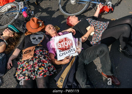 London, UK. 13th October 2018. People, including Donnachadh McCarthy (in pink shirt) of Stop Killing Cyclists take part in a ten-minute die-in outside Parliament at the end of the funeral procession of cyclists behind a horse-drawn hearse to highlight the failure of governments from all the major parties to take comprehensive action on safer cycling. Stop Killing Cyclists call for £3 billion a year to be invested in a national protected cycling network and for urgent action to reduce the toxic air pollution from diesel and petrol vehicles which kills tens of thousands of people every year, and - Stock Image