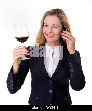 Smiling European business women in her 40's talking on the phone and having a glass of wine - Stock Image