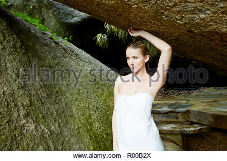 Young woman wrapped in white towel by rocks - Stock Image