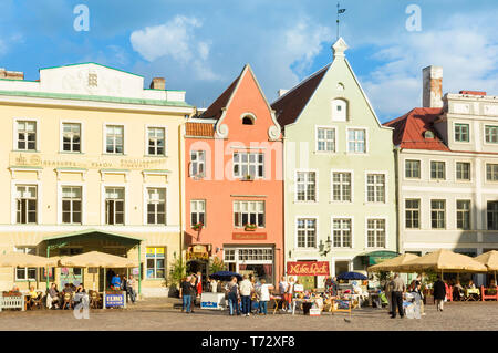 People in Cafes with umbrellas in the medieval cobbled old town square Raekoja Plats Tallinn Estonia Baltic States - Stock Image