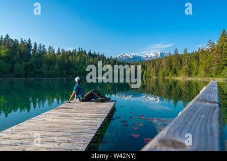 Man relaxing on platform enjoying the view of Cresta lake (Crestasee), Films, canton of Graubunden, Switzerland - Stock Image