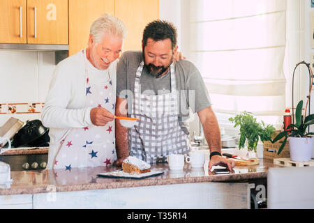 Caucasian couple at home preparing a cake together - father and son adult and senior working in the kitchen - cooking men chef at work with joy and ha - Stock Image