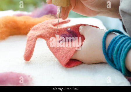 Process of felting. felted decoration made of wool with a traditional felting needle - Stock Image