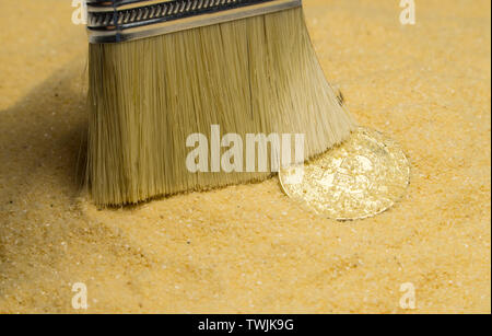an archaeologist with a brush clears the bitcoin coin on the golden sand - Stock Image
