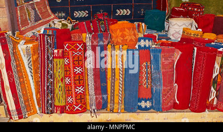 A display of colourful traditioal decorated carpets In the Souk the Street Market at Jemaa el Fnaa in the Medina Old City in the centre of Marrakech i - Stock Image