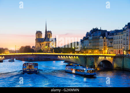 Paris, Tour boat on the Seine river at sunset with Notre Dame de Paris Cathedral in Background - Stock Image