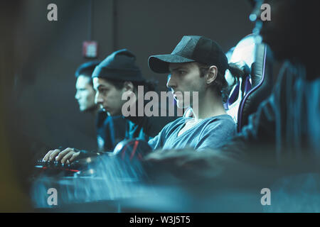 Serious focused young man in cap sitting in row of programmers and working on software in database center - Stock Image