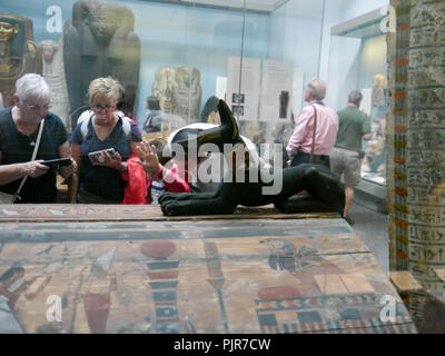 Visitors to the British Museum in London, England look at exhibits in the Egyptian collection - Stock Image