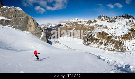 Scenic shot of a single skier on Mount Marmolada approaching Fedaia lake, Dolomites, Italy - Stock Image