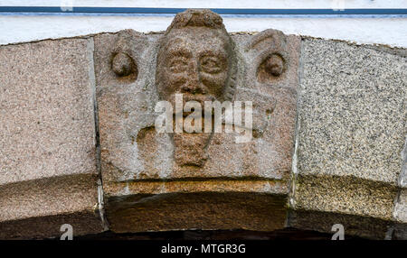 Carved stone head detail on a 15th Century building in Morlaix, Brittany, France. - Stock Image
