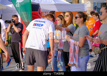 Split Croatia, April 25, 2019 : After the finish line at B2Run Business race,Volunteers handing medals to race finishers - Stock Image