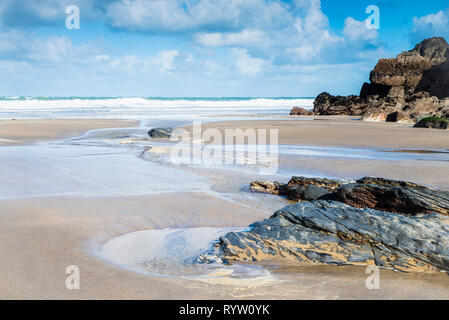 A fresh bright and breezy day in a quiet sandy cove on the North Cornish coast with sand, pools and rocks in the foreground. - Stock Image