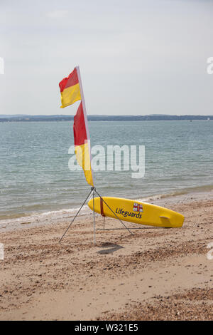 A life Guard flag and surfboard on a beach - Stock Image