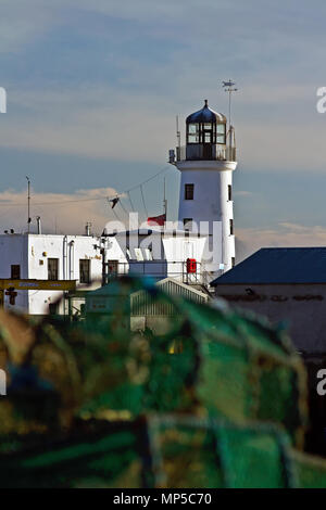 Lobster Pots and Lighthouse. Scarborough's lighthouse and harbour entrance in bright sunshine behind a foreground pile of lobster traps. - Stock Image