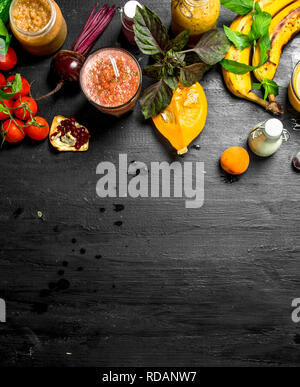 Summer smoothies of vegetables, berries and fruits. On black background. - Stock Image