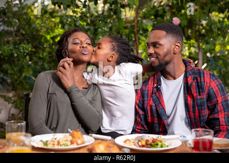 A family eating together, daughter kissing mother on the cheek - Stock Image