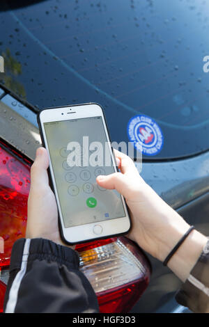 Young woman calling for roadside assistance on her iphone6 plus. AAA Automobile club southern California membership - Stock Image