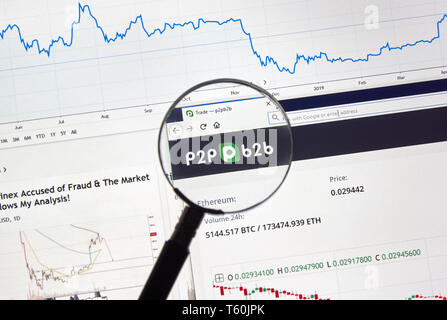 MONTREAL, CANADA - APRIL 26, 2019: p2pb2b cryptocurrency digital assets exchange logo and home page on a laptop screen under magnifying glass. - Stock Image