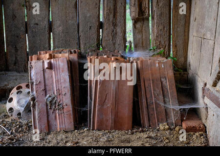 roof tiles stacked inside an old outhouse zala county hungary - Stock Image