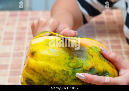 Woman cleans papaya fruit from the peel - Stock Image