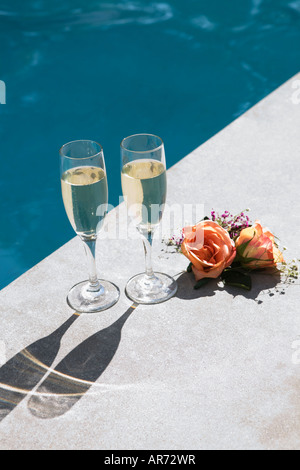 Champagne glasses beside swimming pool - Stock Image