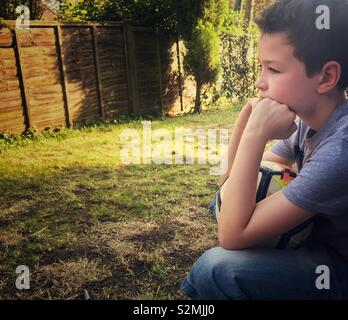 A nine-year-old boy sits deep in thought, resting his chin on his hands, while holding a football on his knee. - Stock Image