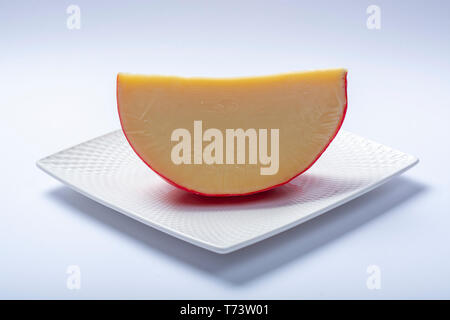 One piece of traditional Dutch red ball Edam cheese close up on white background - Stock Image