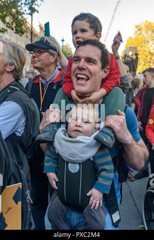 London, UK. 20th October 2018. A man carries two children as he shouts on Whitehall at the end of the People's Vote March calling for a vote to give the final say on the Brexit deal or failure to get a deal. They say the new evidence which has come out since the referendum makes it essential to get a new mandate from the people to leave the EU. With so many on the march the crowding meant many failed to reach Parliament Square and came to a halt in Whitehall. Peter Marshall/Alamy Live News - Stock Image