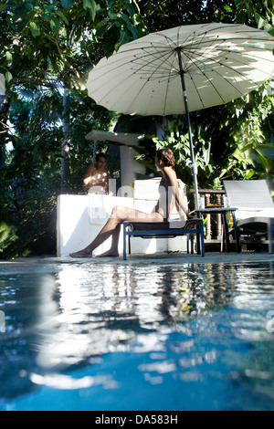 A couple relaxing poolside. - Stock Image