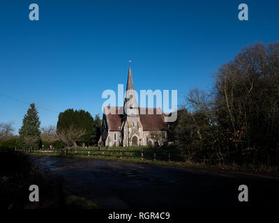 English country church with spire against blue sky. St James Barkham - Stock Image