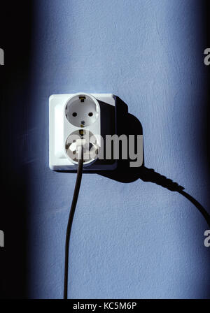 Electrical plug socket with electric cable inserted into one of the plugs with a blue wall background and sunlight - Stock Image