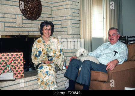 Middle Aged Couple and Their Dog Relax in the Living Room, USA - Stock Image
