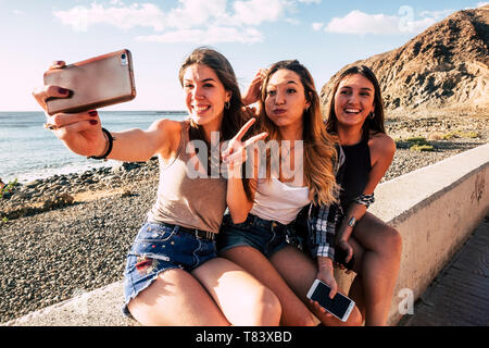 Millennial girls taking selfie picture with modern phone for social media having lot of fun together in friendship - smile and crazy expression people - Stock Image