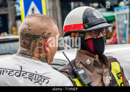 Phuket, Thailand 17th January 2019: Man with tattooed head talking with policeman in Patong Beach. Police often fine tourists for traffic offences. - Stock Image