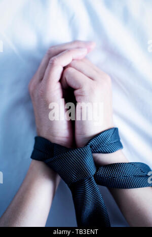 closeup of the hands of a caucasian man, lying face up on a bed with white linen, tied up with a gray necktie - Stock Image