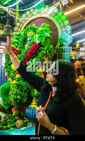 Worshiper Ringing Bell while Circumambulating Hanuman Shrine, Sree Veera Hanuman Hindu Temple, Kuala Lumpur, Malaysia. - Stock Image
