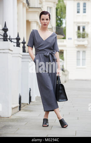 Chic businesswoman in jumpsuit standing in London street - Stock Image