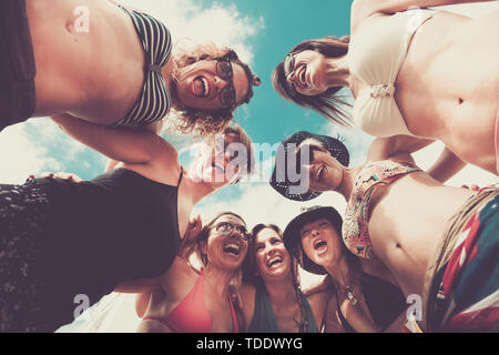 Alternative ground view of cheerful female young people - group of friends women laugh and have fun together viewed from floor - blue sky in backgroun - Stock Image