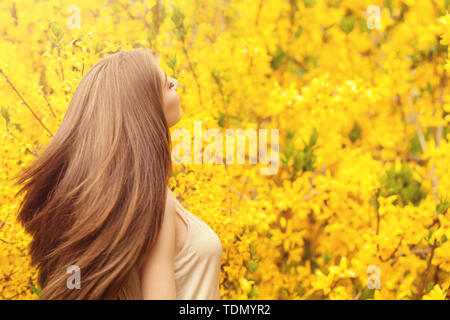 Romantic portrait of beautiful woman with long blowing hair on floral background - Stock Image