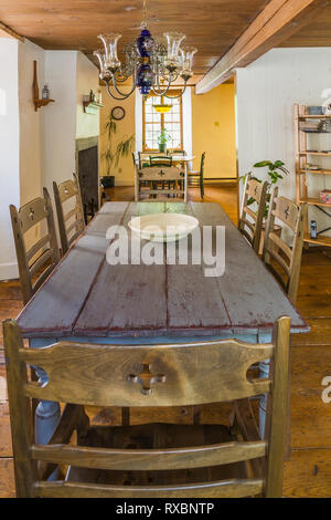 Wide plank wooden dining table with empty white ceramic bowl and high back chairs in dining room inside an old circa 1760 Canadiana fieldstone cottage - Stock Image
