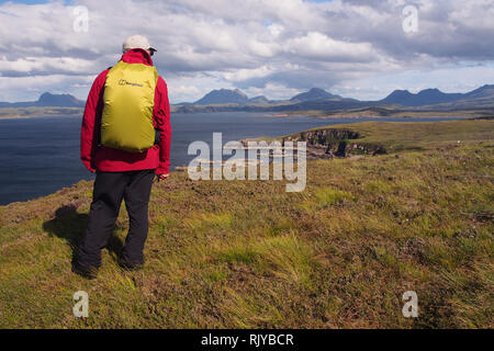 A male lone rambler viewing the scenery on the Coigach Peninsula, Scotland wearing a red coat and a yellow covered backpack, with mountains and sea. - Stock Image