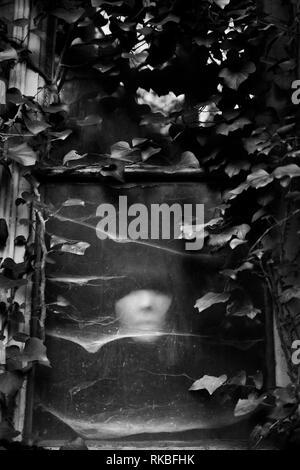 Masked girl behind abandoned house building window - Stock Image