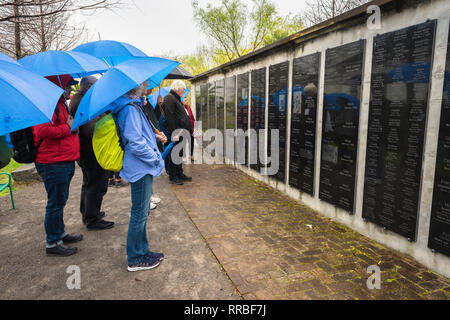 A tour group in the rain at Whitney Plantation Museum views the Wall of Honor, a monument bearing the names of 350 slaves who worked on the site, USA - Stock Image