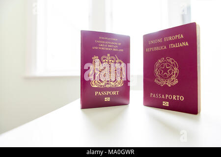British and Italian passports standing next to each other, with white light exploding in the background. Framed on the right with negative space. - Stock Image