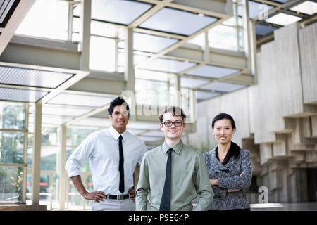 A portrait of a mixed race team of business people standing in the lobby area of a convention center. - Stock Image